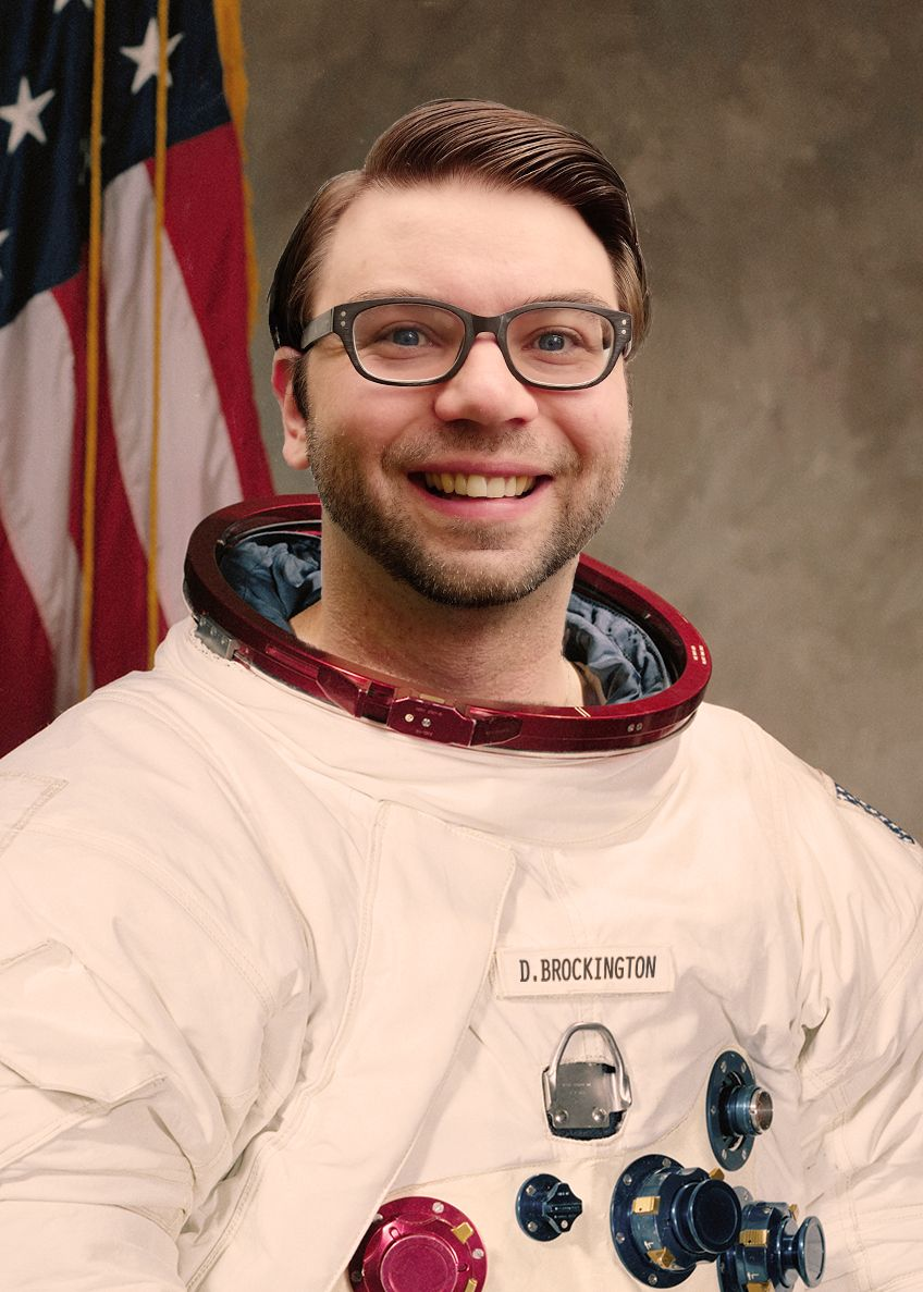 White man with brown hair and glasses in a white space suit with red collar.